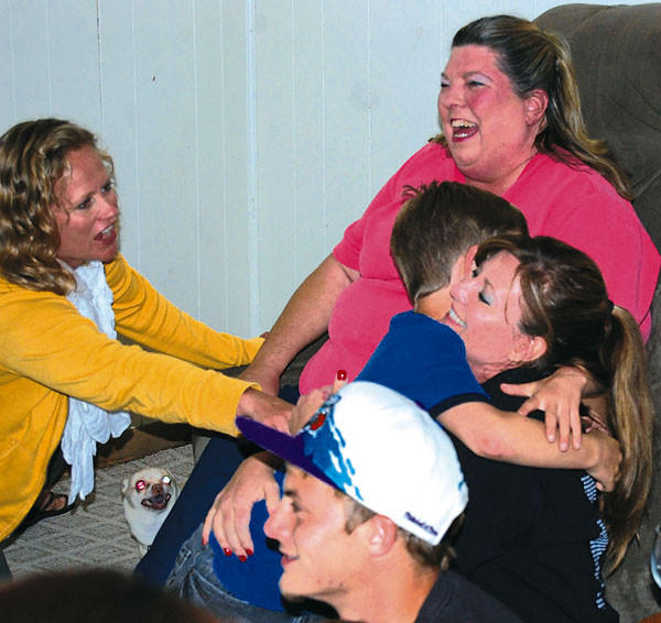 "Lisa Johnson of Lincoln County gets a congratulatory hug Friday night as friends and family react after seeing her win $10,000 on the TV show, ""The Singing Bee."""
