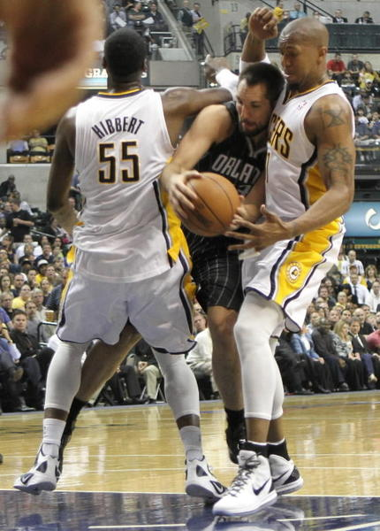 Orlando Magic forward Ryan Anderson tries to get past Pacers players Roy Hibbert and Darren Collison.