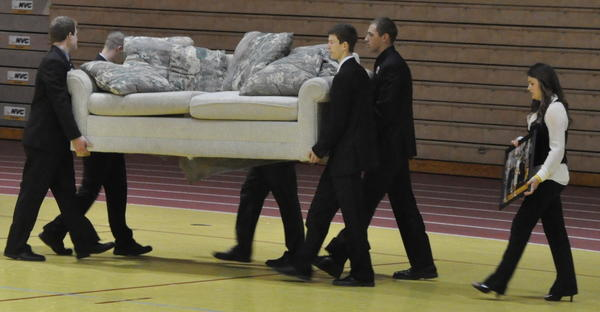 Bryce Anglin's casketbearers bring in the couch where Baseline Bandits sat during home basketball games jokingly harassing opponents and officials. Anglin, who was a member of the Bandits, died of cancer April 24. Hundreds of mourners said goodbye Monday at Wach's Arena. American News Photo by Anita Meyer