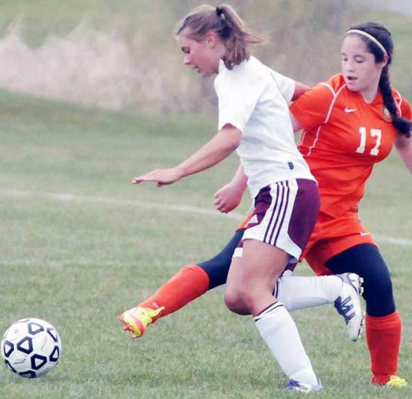 Carolena Elowsky (white jersey) of Charlevoix tries to work around Harbor Springs freshman Sophie Seitz Monday during a 4-2 Rayder win.