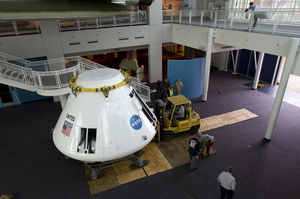Riggers roll the Orion test module onto the bottom floor of the Virginia Air and Space Center Tuesday.