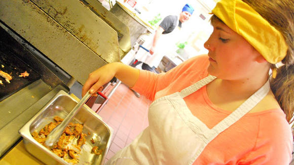 Culinary arts student Lynsey Kassuba takes her Jamaican jerk carp off the grill. She said she doesn't eat fish much but noted the spicy fish reminded her of the texture of pike.