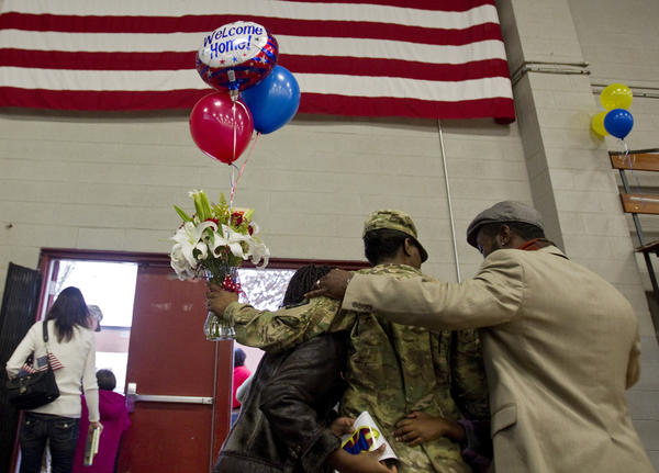 (Left to right) Tijonah Dixon, Staff Sgt. Tiffany Dixon and John Dixon exit Fort Eustis' Anderson Field House following the return of 200 soldiers of the 7th Sustainment Brigade. The soldiers returned to Fort Eustis Saturday, Feburary 11, following a year-long deployment in Afghanistan.