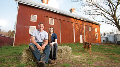 John Dove and his girlfriend, Courtney Costantino, sit by a barn that predates the Dove family's purchase of the Woodbine farm. For years, the Doves participated in conventional farming, first in dairy, later in grain and soy crops. In 2010, Dove began growing organic vegetables on two of the 200 acres.
