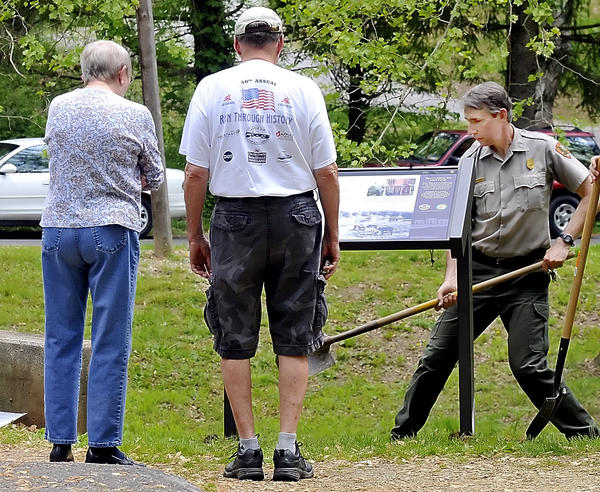 Regina and Lou Clark, left, look over a wayside marker as Curt Gaul, West District Ranger for the Chesapeake & Ohio Canal National Park, fills holes at the marker that was placed at Snyder's Landing near Sharpsburg on Tuesday.