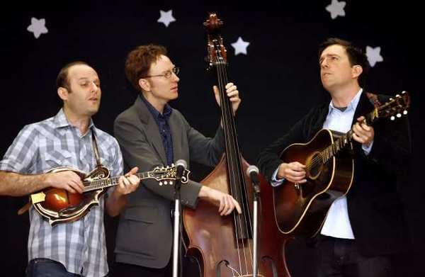 Actor and musician Ed Helms, right, sings along with his group the Lonesome Trio (Jacob Tilove, left, and Ian Riggs, center) during a visit to Providencia Elementary School in Burbank.