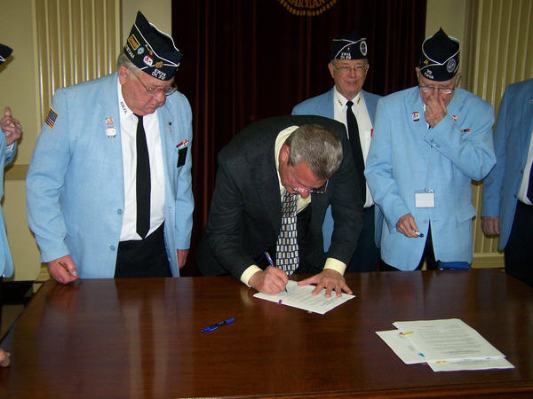 Hagerstown Mayor Robert E. Bruchey II, center, signs a resolution Tuesday to build a Korean War memorial at the corner of Potomac Avenue and Mealey Parkway. Standing behind the mayor are members of the Korean War Veterans Association, Antietam Chapter 312, from left to right: Commander Jim Ensminger, Vice Commander Les Bishop and Jim Mobley, chairman of the monument committee.