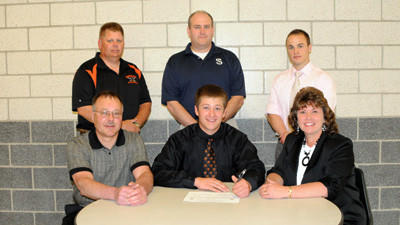Austin Sleek, front middle, signs his letter of intent to play baseball at Seton Hill University Tuesday as his parents Homer and Beth Sleek look on. In back are coaches Steve Costea, Bob Hay and Dan Delsignore.