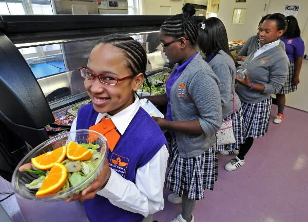 Cauriel Bocage (CQ,) left, a 6th grade student, created a big salad topped with orange wedges for lunch at Baltimore Leadership School for Young Women. The school offers a salad bar as part of its cafeteria offerings.