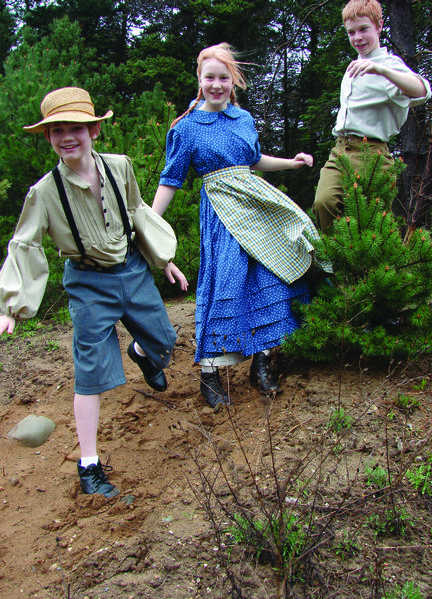 Running through the countryside are area homeschoolers (from left) Landon Brantly of Petoskey as Warren Woodlawn, Ella Ruthig as Caddie and Tom Ruthig as older brother Tom Woodlawn, both from Levering.