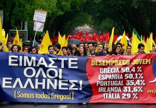 "Young protesters carry a banner bearing the slogan ""We are all Greek"" and statistics for youth unemployment in some European Union countries during a march in Lisbon on April 25. Euro zone unemployment is now at a record high since the euro debuted in 1999."