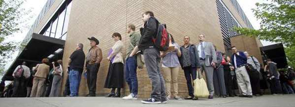 Job seekers wait in line during a job fair in Portland, Ore., in April.