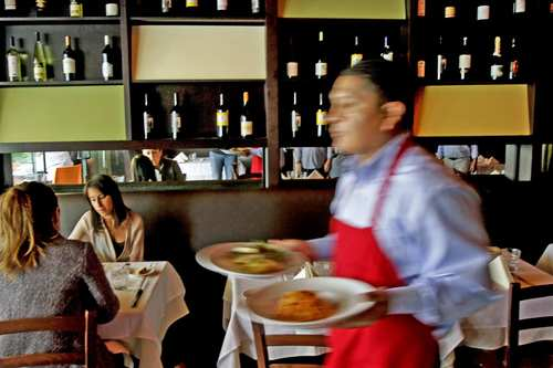 A waiter delivers meals in one of the dining rooms in the space that previously was Il Buco.
