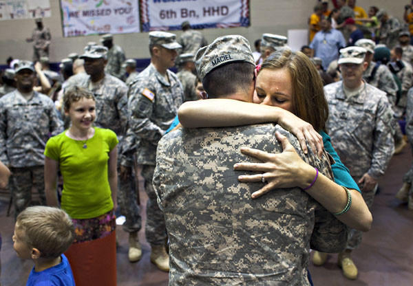 Stephanie Maciel welcomes her husband, Spc. Joshua Maciel at Fort Eustis on Thursday as he and other soldiers return from supporting Operation New Dawn.