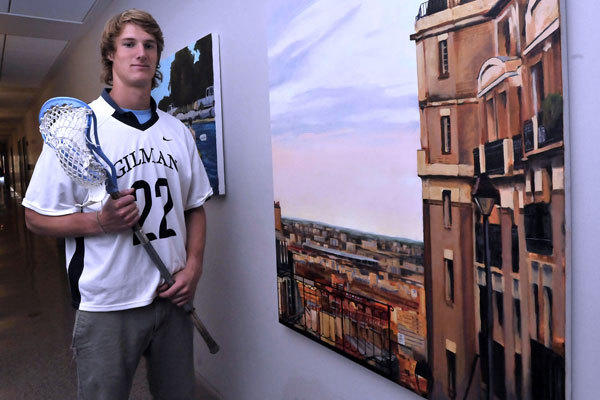 "Gilman senior lacrosse player Jake Matthai poses with one of the oil paintings he did for his senior thesis in a studio art class. ""Paris,"" on a 48 x 36 canvas, is one of several pieces of art hanging in a hallway of the school."