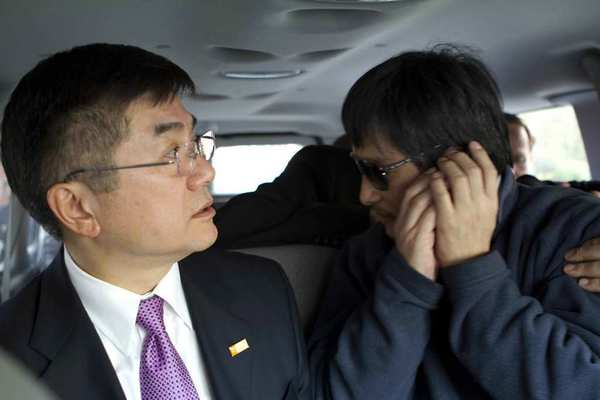 Chinese dissident Chen Guangcheng speaks on a phone as U.S. Ambassador to China Gary Locke, left, looks on, in Beijing.
