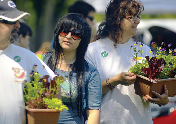 Kevin, Kelsey and Sandy Pifer of Keedysville buy some plants and look at the environmentally friendly vendor, during last years Boonsboro Green Fest at Shafer Park in Boonsboro. This years event will take place Saturday, May 12.