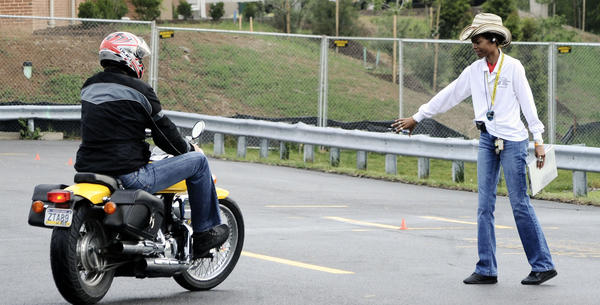 Instructor Dawn Douglas, right, gives Holger Haber directions at his motorcycle driving test Wednesday morning as part of Maryland's Fast Track program.