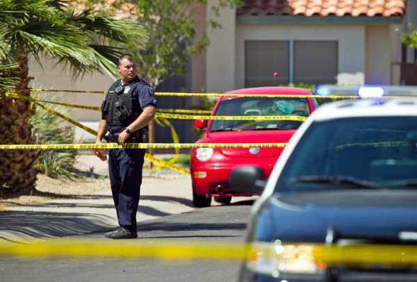 A police officer stands outside a house where five people, including a toddler, were found shot to death, in Gilbert, Ariz.