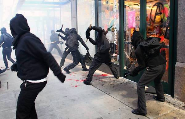 Protesters break windows of downtown Seattle businesses during a May Day rally Tuesday.