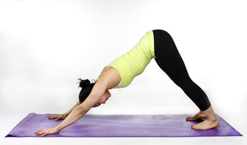 "Start on your hands and knees. Lift the hips up and back to straighten your legs. Keep your arms straight with your chest relaxing back toward your feet and head between your arms. <br /><br />""If you're sitting at a computer all day, downward-facing dog is good because it stretches your legs and back,"" Yang says. Downward-facing dog is a great stretch for your calves and hamstrings."