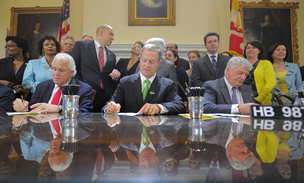 """Maryland Senate President Thomas V. """"Mike"""" Miller (left) and Speaker of the House Michael Busch (right) flank Gov. Martin O'Malley as they sign bills Wednesday. The three have reached some consensus on bringing legislators back to Annapolis for an additional Assembly session."""