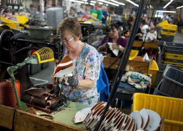 In Ada, Ohio, workers sew together leather panels that will form footballs. Worker productivity is down the most in a year -- but that's because employers hired more people.