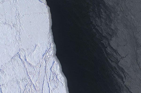The margin of a large lead of open water (dark) and thin grease ice (gray, right) in the Chukchi Sea between Alaska and Russia. The image was create using several frames from the Digital Mapping System (DMS) onboard the NASA P-3. Image: NASA/DMS/Eric Fraim.