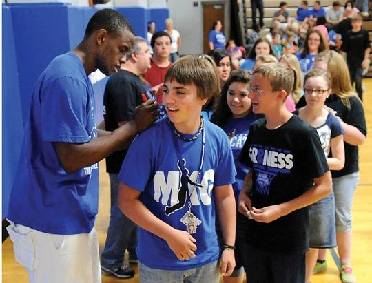 University of Kentucky basketball standout Darius Miller visits Clark Middle School Thursday morning where he signed the UK t-shirt of Trevor McCarty. Miller also visited Strode Station and Central elementary schools and Conkwright Middle School. Miller, and the rest of UK's eighth National Championship team, will visit the White House and President Barack Obama on Friday and then he will graduate from UK on Sunday.