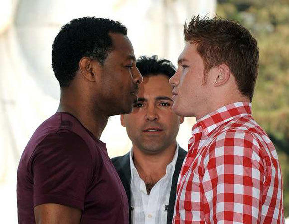 "With boxing legend Oscar De La Hoya looking on, Shane Mosley, left, and Saul ""Canelo"" Alvarez face off in a pre-fight staredown at a Wednesday news conference at the MGM Grand in Las Vegas."