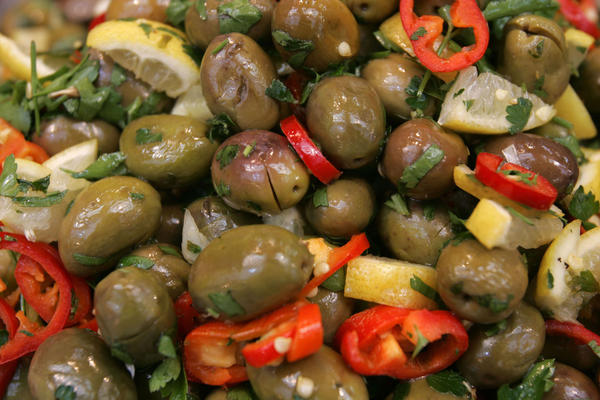 A vendor's own blend of green olives with lemons, red chili peppers and parsley is displayed for sale at a delicatessen. Olives and olive oil, a source of monounsaturated fat, which is protective against heart disease, and also a source of antioxidants including vitamin E, are staple foods in Mediterranean countries.