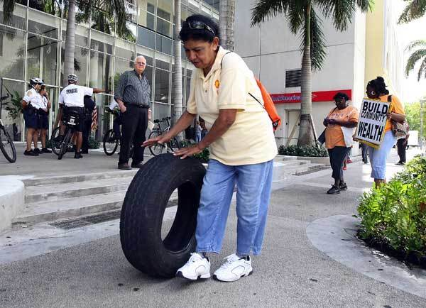 Hermenia Nasser rolls a tire past the Bank of America on Flagler Street in downtown Miami.  Activists in Miami cleaned up trash at a Bank of America property in Liberty City and then delivered the trash to a downtown branch of the bank.