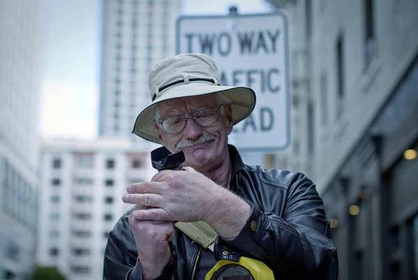 Leaning on a parking meter, Mark Ellinger adjusts his camera to photograph some of his favorite architecture in San Francisco's Tenderloin district.