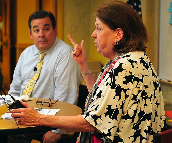 Washington County Public Schools Superintendent Clayton Wilcox, left, listens Thursday as Mary Baykan, director of the Washington County Free Library, speaks Thursday at a literacy summit in Hagerstown.