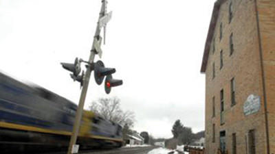 An Amtrak study suggests the company could make money with a stop in Rockwood. A train is shown passing the Rockwood Mill Shoppes & Opera House.