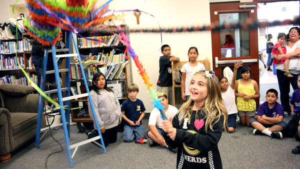 Isabel Putrus, 9, takes her turn at hitting a pinata at the Cinco de Mayo story time celebration Thursday at Calipatria Library.