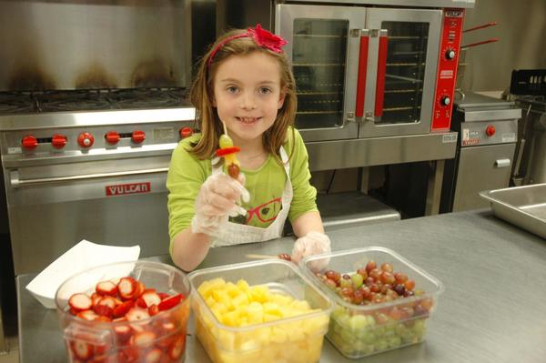 Megan Novak, 8, makes fruit kabobs as part of a healthy menu. She recently won the chance to serve the menu she designed to her classmates at Harbor Springs's Blackbird Elementary.