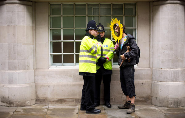 "A protester speaks with two policemen outside a hotel near St Paul's Cathedral in central London on May 3, 2012 during a demonstration against the use of fossil fuels and the policies of energy firms attending the The UK Energy Summit conference.  Over a hundred Climate protesters and anti-cuts demonstrators attempted to disrupt a summit of major energy firms in the City of London over high energy bills and greenhouse gas emissions. Campaigners attempted to enter the venue of the conference being attended by the heads of six energy companies with banners and giant model dinosaurs to highlight the ""dinosaur technology"" of fossil fuels."