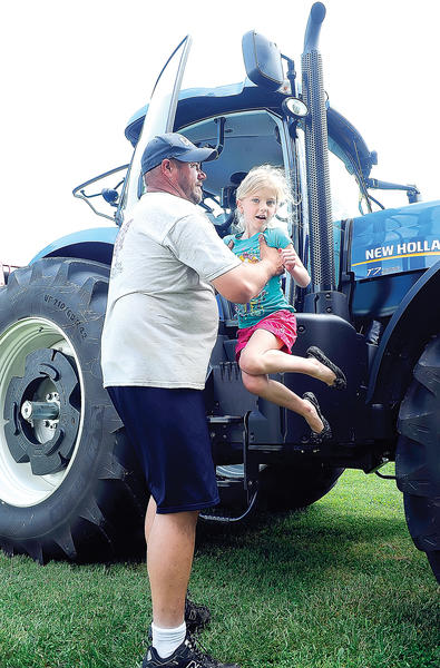 Smithsburg Elmentary School kindergartner, Olivia Rohrer, is assisted down from this giant New Holland T7.270 tractor Friday during the Smithsburg High School FFA Farm Day by volunteer Norman Potter of Smithsburg.