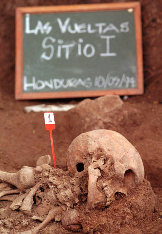 "A marker placed by forensics expert near the first of five sets of skeletons exhumed at a mass grave site in <a class=""taxInlineTagLink"" id=""PLGEO00000184"" title=""Honduras"" href=""/topic/international/honduras-PLGEO00000184.topic"">Honduras</a>. This is the first ever dig in Honduras to try to exhume and identify remains of the disappeared from the 1980s"