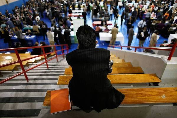 A man takes a break at a job fair in New York. The unemployment rate inched down to 8.1% because more discouraged workers dropped out of the labor market.