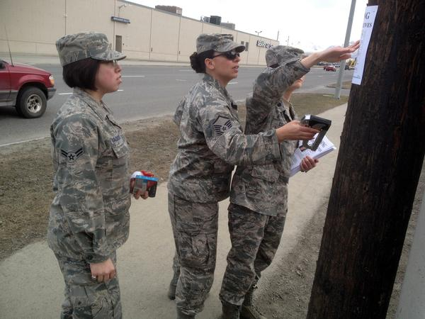A team posts fliers with a photo of missing airman Clinton Reeves, along Northern Lights Blvd. in Anchorage.