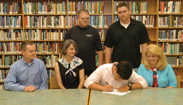 George Rogers Clark senior Raymond Borja signs a national letter-of-intent to play soccer at Transylvania University Friday afternoon. Borja is joined on the front row, from left by uncle, Marc Ford; aunt, Cindy Ford; and mother, Mona Willoughby; back row, Transylvania men¿s soccer coach Sam Wooten; and former Clark boys soccer coach Patrick Fitzgerald.