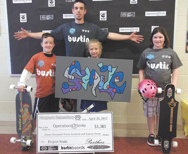 The three Pangborn Elementary School students who raised the most for Project Smile are, from left, third place, Bobby Lopez, $139; second place, Olivia Tracy, $159; and first place, Hannah Zeger, $203. Project Smile organizer Andy Iverson, an art teacher at the school, is in the rear.