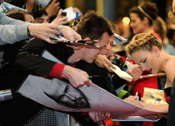 "Scarlett Johansson signs autographs for fans as she arrives for the European premiere of ""The Avengers"" in London."