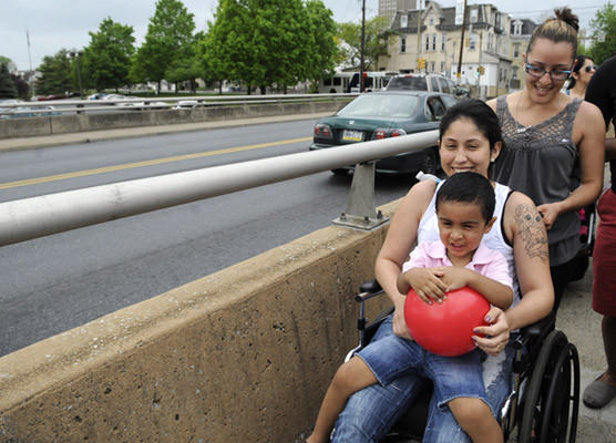 Ruth Aragon of Allentown who jumped from the 8th Street Bridge in September sits in her wheelchair as she is pushed across the bridge by her friend Janet Valentin of Allentown. In Ruth's lap is her nephew Matthew Hilario, 3.  Marchers held this prayer walk to call for barriers to be constructed to prevent suicides by people jumping from the 8th Street Bridge.