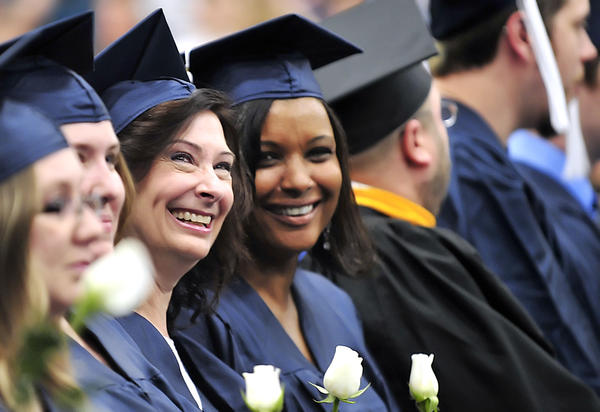 Valerie Palmer, third from left, and Pamela Raynor smile while looking in the audience, Saturday during Penn State Mont Alto commencement at the Multipurpose Activities Center on campus at Mont Alto.