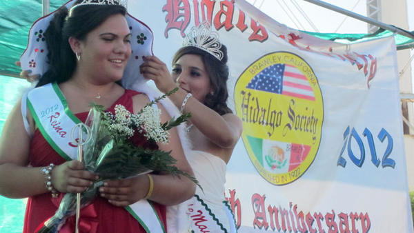2011 Cinco de Mayo queen Jocelyn Nunez fixes the robe of 2012 queen Amanda Rae Garcia after crowning Amanda the new queen Saturday evening.