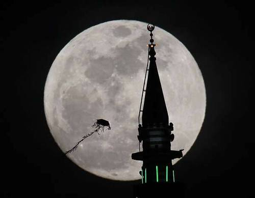 The full moon rises behind a mosque as a kite flies in Jordan.