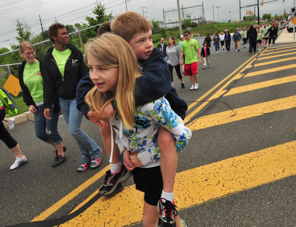 Reagan Smith 10, of Breinigsville carries brother Luke, 6, on LSI Way as they join over 2000 in Sunday's Walk MS, which began and ended at Coca Cola Park in Allentown. The 3 mile walk raised over $250,000 to raise funds for research to find a cure for multiple sclerosis,.
